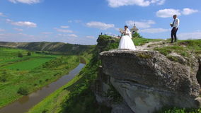 Groom holding bride`s bouquet approaching to bride standing on a cliff above river.  stock video