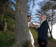 Groom Holding Bride's Hand Behind Tree. This groom is holding the bride's hand while she is standing behind a tree in this beautiful photo in a natural setting Stock Photos