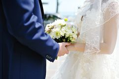Groom holding the bride's hand and wedding bouquet Stock Photography