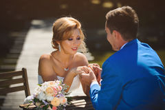 Groom Holding Bride`s Hands. At table on bridge Stock Images