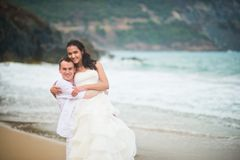 Groom is holding the bride by the sea. couple in love on a deserted beach royalty free stock photo