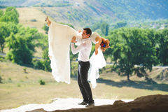 Groom Holding Bride on Shoulder. On hill Stock Photo