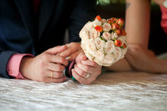 Groom is holding brides hand and wedding bouqet. Groom is tenderly holding his bride hand. In his other hand he has wedding bouqet Royalty Free Stock Photography