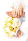 Groom holding brides hands on the bouquet Royalty Free Stock Image