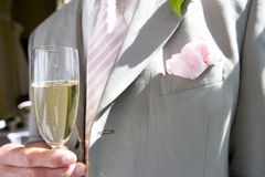 Groom holding champagne flute, close-up, mid section Royalty Free Stock Image