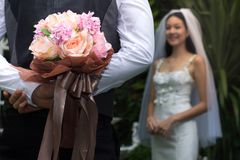 Groom holding Colorful wedding bouquet in his back to surprise Bride,Close-up bunch of florets. /Marriage concept Royalty Free Stock Photos