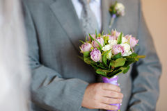 Groom holding flowers Royalty Free Stock Images