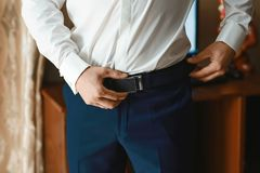 Groom holding hands on the belt, wedding suit stock photos