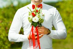 Groom holding in hands delicate, expensive, trendy bridal wedding bouquet of flowers in red and white.  Stock Image