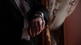 Groom is holding hands on the tie, wedding suit. close up of a hand man how wears white shirt and cufflink. Business man stock video