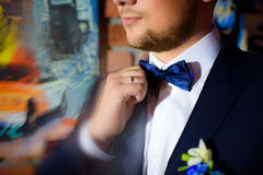 Groom holding his bow tie with his hands. Blue black Royalty Free Stock Images