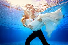The groom is holding his bride in white dress on background of sun rays underwater in the pool. Horizontal orientation. A view from under the water from the Royalty Free Stock Image
