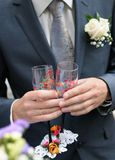 Groom is holding painting champagne glasses Royalty Free Stock Images