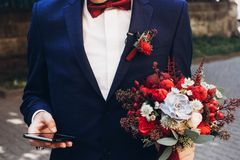 Groom holding phone and bouquet with red roses and succulents in. Other hand in the morning. rustic flowers. boho newlyweds stock photo