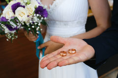 Groom holding rings in palm. Near bride bouquet Royalty Free Stock Photo