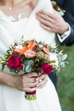 Groom  holding shoulder of bride with red rose bouquet in hands Stock Images