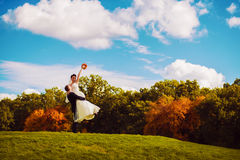 Groom holding smiling bride on field Royalty Free Stock Image