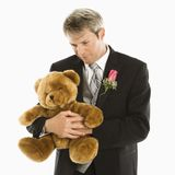 Groom holding teddy bear. Stock Images