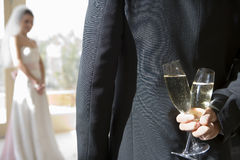 Groom holding two champagne flutes behind back, bride standing in background, focus on groom in foreground, rear view Royalty Free Stock Photos