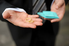 Groom holding two gold wedding rings Stock Photos