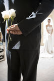 Groom holding two white roses behind back, bride standing in background, focus on groom in foreground, rear view Stock Photography