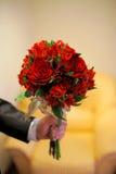 Groom holding wedding bouquet Stock Photos