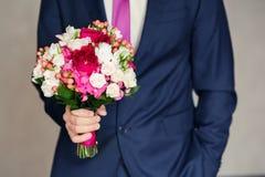 Groom holding wedding bouquet Royalty Free Stock Photos