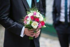 Groom holding wedding bouquet of his bride Stock Photo