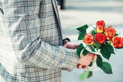 Groom holding a wedding bouquet of orange roses. Groom dressed in checkered jacket holding a wedding bouquet of orange roses Royalty Free Stock Image