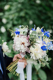 The groom holding a wedding bouquet of peonies. On which stag beetle sitting Stock Images