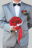 Groom holding wedding bouquet of red roses flowers in suit and bow tie Stock Photos