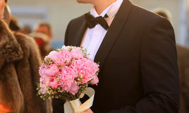 Groom holding wedding bouquet Stock Images