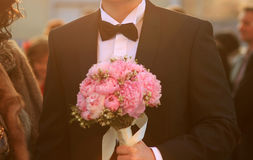 Groom holding wedding bouquet Stock Image