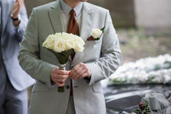 Groom holding a wedding bouquet of white roses Royalty Free Stock Photos