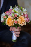Groom holding a wedding bouquet of yellow roses, pink roses Stock Images