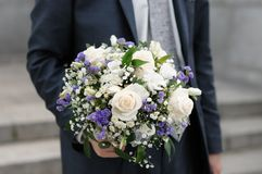 Groom holding wedding flowers bouque Royalty Free Stock Images