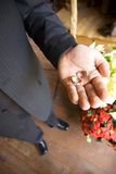 Groom Holding Wedding Rings. In his palm.  Focus on groom's hand.  High viewpoint looking down Stock Image