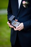 Groom holding wedding rings. Groom holding his and bride's wedding rings in the black box Stock Photo