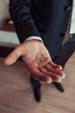 Groom holding wedding rings Stock Photo