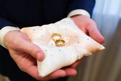 Groom holding wedding rings Stock Image