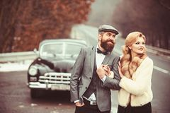Groom holds an arm of a charming bride while walking at retro car. stock photos