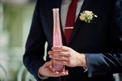 Groom holds bottle with pink sand at wedding stock images