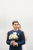Groom holds  bouquet  bride  puting hands  on his shoulders Stock Photo