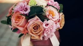 The groom holds the bridal bouquet in his hand. Ribbons sway in the wind. Closeup stock video