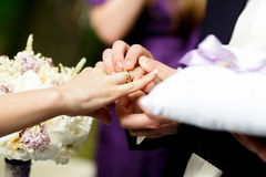 Groom holds bride arm tenderly while he puts a wedding ring on h Royalty Free Stock Image