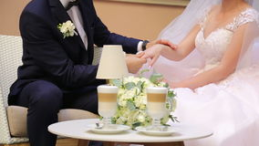 Groom holds the bride by the hand, next to two cups of coffee cappuccino stock video footage