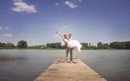 The groom holds the bride on hands. A happy newly-married couple on river jetty Royalty Free Stock Images