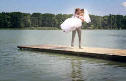 The groom holds the bride on hands. A happy newly-married couple on river jetty Stock Photography