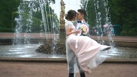 The groom holds the bride in his arms and kisses on the background of the fountain stock video footage
