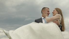 Groom holds bride in his arms on sky background. Wedding couple. Happy family stock video